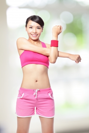 asian sport: Fit woman stretching her arm to warm up on green background, model is a asian girl