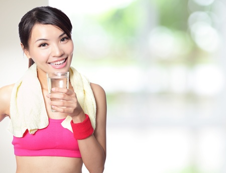 chinese drinks: sport girl drinking water after sport with nature green background, model is a asian woman Stock Photo