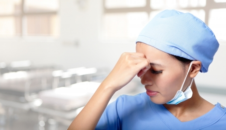 hospital stress: unhappy upset woman medical doctor or nurse sad and depressed having stress breakdown in hospital. female Asian model Stock Photo