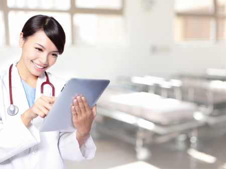 happy patient: surgeon woman doctor smile using tablet pc in hospital, model is a asian beauty