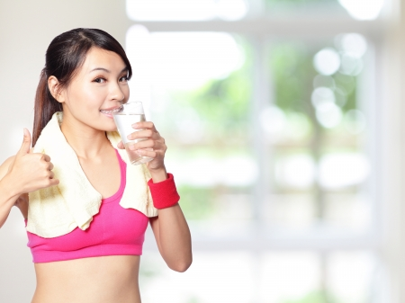 asian sport: sport girl drinking water and show thumb up after sport with nature green background, model is a asian woman Stock Photo