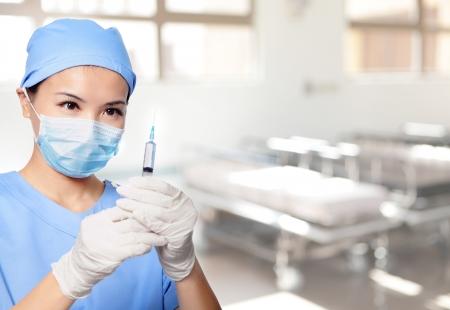surgical needle: surgery woman doctor holding syringe needle in hospital, asian female model