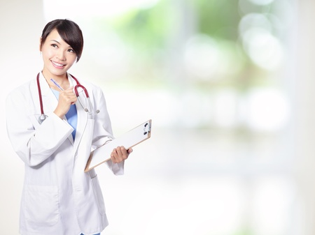 medical doctor woman smile think looking up with stethoscope and clipboard, nurse wear blue surgery suit. with nature green  background, asian beautiful female model photo