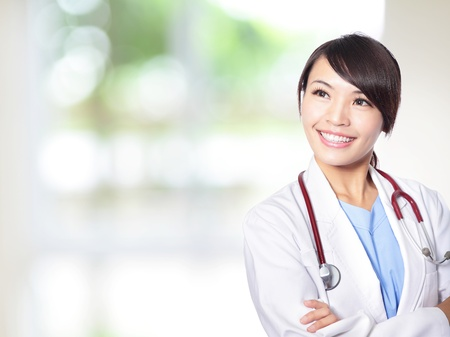 asian nurse: Portrait of beautiful laughing female doctor smile look to empty copy space with nature green background Stock Photo