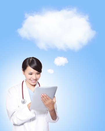 Woman doctor smile using tablet pc computer with blue background and white cloud (great for text copy space), concept for cloud computing technology on health care,  model is a asian female photo