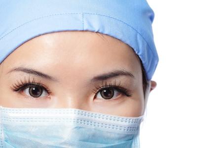 quir�rgico: Primer plano retrato de mujer seria enfermera o m�dico rostro en m�scara quir�rgica aislada en el fondo blanco, modelo es una hembra asi�tica