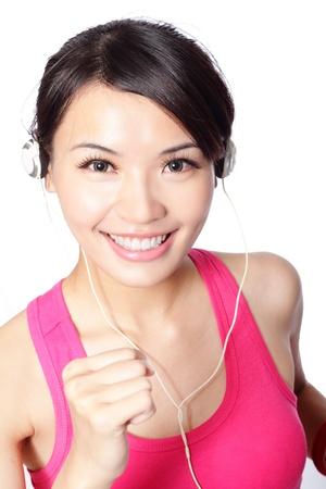ecoute active: Jeune femme en v�tements de sport jouit et sourit �coute de la musique avec des �couteurs blancs. mod�le asian girl Banque d'images