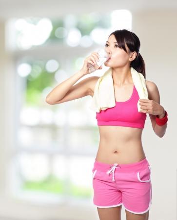 자연 녹색 배경으로 스포츠 후 물을 마시는 스포츠 소녀 모델은 아시아 여자입니다 스톡 콘텐츠