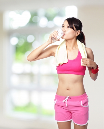 bebidas frias: chica deporte de agua potable despu�s del deporte con la naturaleza de fondo verde, modelo es una mujer asi�tica