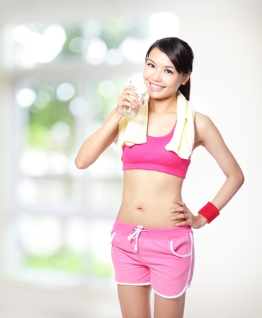 sport girl drinking water after sport and smile to you with nature green background, model is a asian woman photo