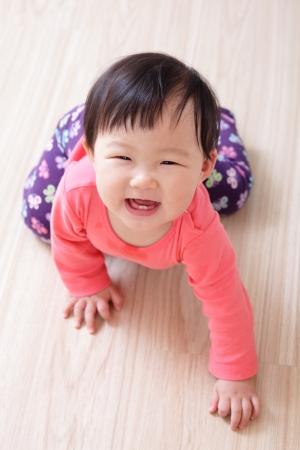 bebe gateando: ni�a gateando en el piso de la sala y ella sonr�e a ti, ni�o asi�tico