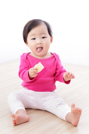 Little Baby Girl eat cookies and sticking her tongue out on living room at home, asian child  photo