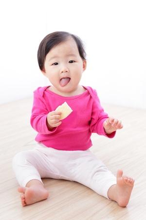 lengua afuera: Peque�o beb� comer galletas y sacando la lengua en la sala de estar en casa, ni�o asi�tico