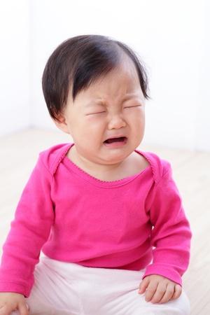 baby huilen: portret van huilende baby meisje op woonkamer thuis, Aziatisch kind