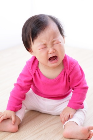 portrait of crying baby girl on living room at home, asian child