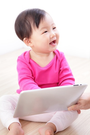 Girl baby happy play game with tablet PC. asian child smile look her mother photo