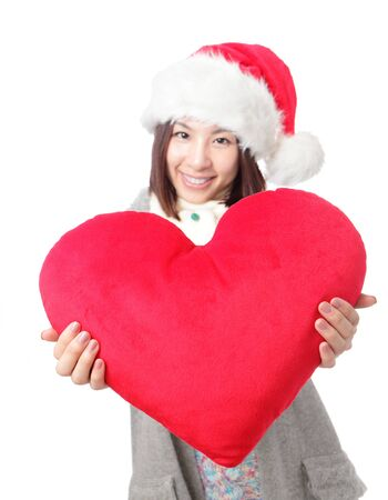 Beautiful girl in Santa hat holding big love heart shape pillow isolated on white background, asian beauty photo