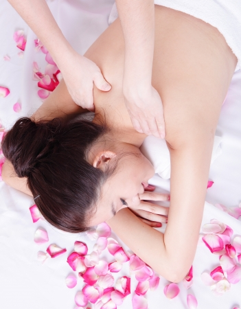 massage face: beautiful asian woman enjoying shoulder spa treatment while lying on a towel with rose flower around