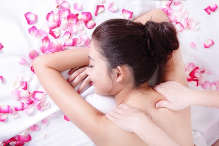 asian woman beauty enjoying shoulder spa treatment with rose flower around photo