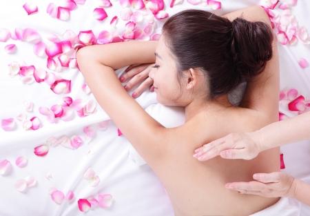 masajes relajacion: mujer joven asi�tica recibiendo masajes y tratamientos spa en la espalda con fondo rosa