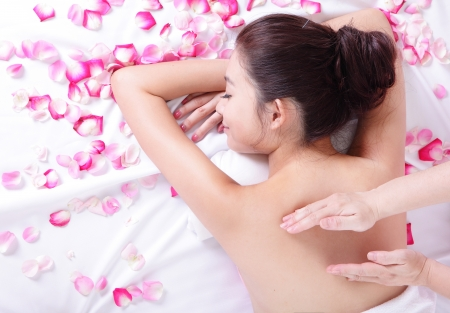 body massage: young asian woman getting massage and spa treatment on her back with rose background