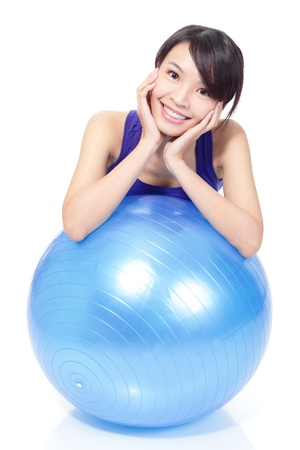 Young beautiful Woman portrait at the gym smiling leaning on a pilates ball in full length isolated over white background, model is a asian girl Stock Photo - 16790931