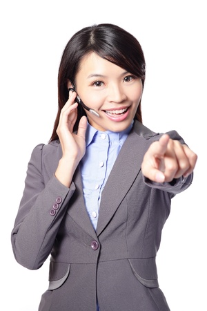 call center agent: business woman with headset and smiling pointing to you isolated on white background, asian woman
