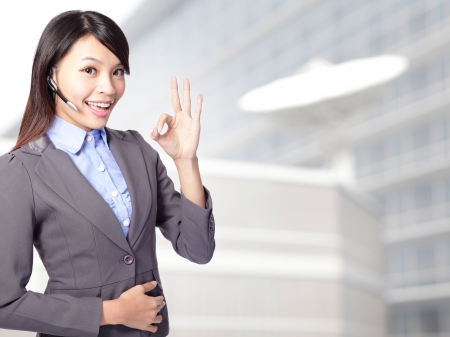 handsfree phone: Portrait of happy smiling cheerful female customer support phone operator in headset showing okay gesture at office, asian woman Stock Photo
