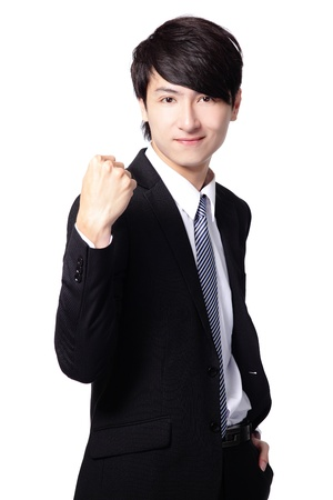 Excited handsome business man with arms raised and showing his fist isolated on white background, mode is a asian people photo