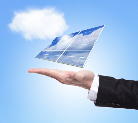 eco concept - Business man hold Alternative Energy (solar cell ) with blue sky and cloud background photo