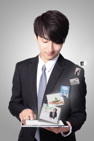 handsome business man using touch screen tablet pc with streaming images, concept for business and cloud computing, asian man model photo