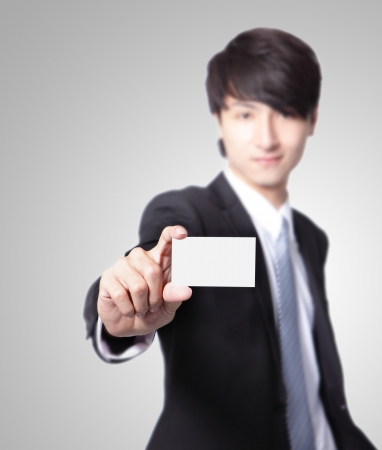 people holding sign: business card in business man hand with smile face ( focus on paper ) isolated on gray background, asian male model