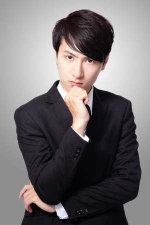 hand chin: portrait of handsome business man with hand on chin, looking at camera on gray background, asian male model