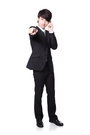 Successful handsome business man speaking mobile phone and finger pointing to you in full length isolated on white background, mode is a asian male photo