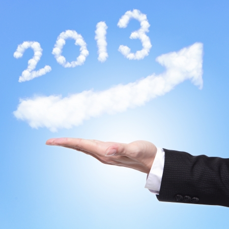 hand of Business man holding happy new year 2013 (white cloud and blue sky on sunny day) on his hand photo