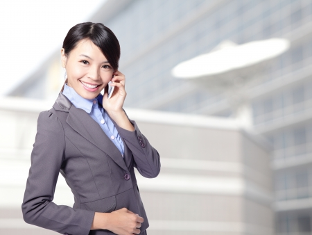 Beautiful smiling business woman speaking mobile phone at office, asian beauty model photo
