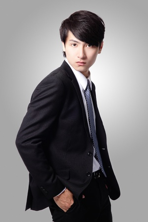 handsome confident business man in suit posing isolated on gray background, asian male model photo