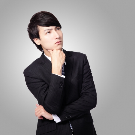 Handsome young business man think looking up to empty copy space, businessman hold hand behind head, wear elegant suit and tie, isolated gray background, asian male model photo