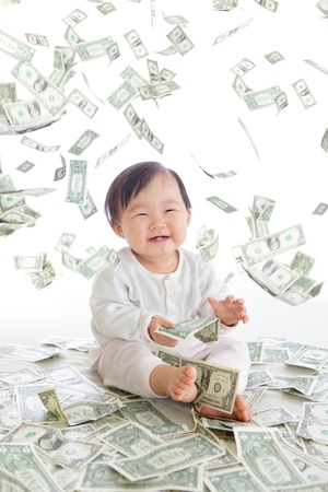 baby excited smile with money rain in the air isolated on a white background, concept for business, asian girl baby child photo
