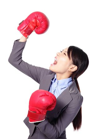 woman screaming: Winning business woman celebrating wearing boxing gloves and business suit. Winner and business success concept isolated on white background. asian beauty model