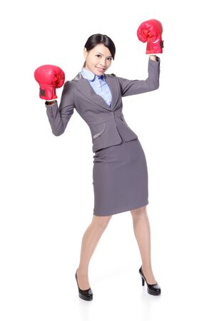 woman boxing gloves: Winning business woman celebrating wearing boxing gloves and business suit in full length isolated on white background. asian beauty model