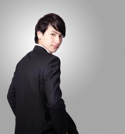 Succesvolle zakenman lachend gezicht en op zoek naar u met grijze achtergrond, model is een Aziatische mannen