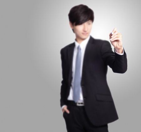 asian businessman: handsome Business man writing with marker pen in the air isolated on gray background, great for you add any text or graph