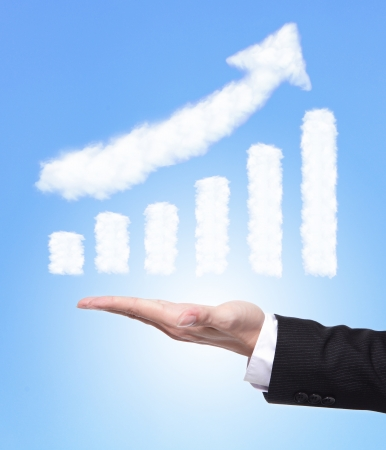 Business man hand holding a growth graph ( made by cloud ) in the air with blue sky, finance and business concept Stock Photo - 17012320