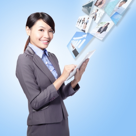 business woman holding a tablet pc and work with internet isolated on blue background, model is a asian girl photo