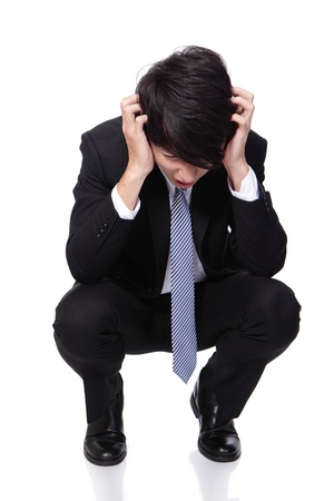 to crouch: Portrait of a young business man looking depressed from work and crouch on the floor isolated on white background, asian model Stock Photo