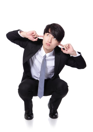 to crouch: businessman hold hands to cover ears and crouch on the floor isolated on white background, asian model, concept of business man stressed, depressed, pain Stock Photo