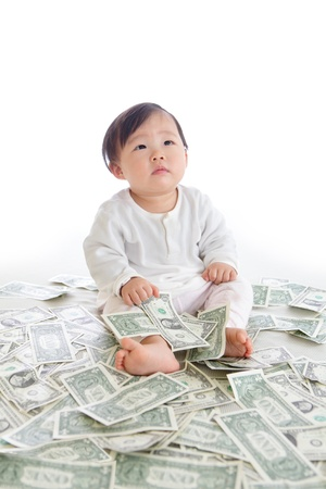 baby sit on floor with many money and look to up empty copy space isolated on a white background, concept for business, asian girl baby child photo
