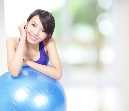 Young happy woman  leaning on a pilates ball with green background, model is a asian girl photo
