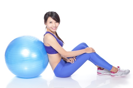 Young happy woman sitting on floor with fit ball in full length isolated on white background, model is a asian girl Stock Photo - 17034674